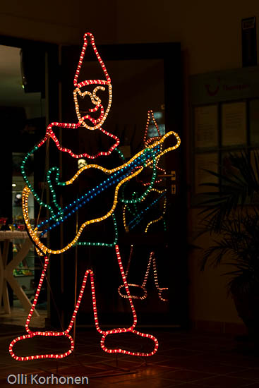 Kuva: valoteos, kitaraa soittava ilveilijä, Kreeta