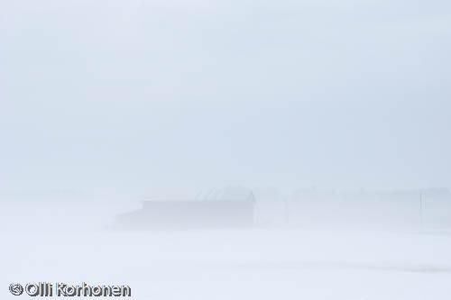 A barn in a fog.