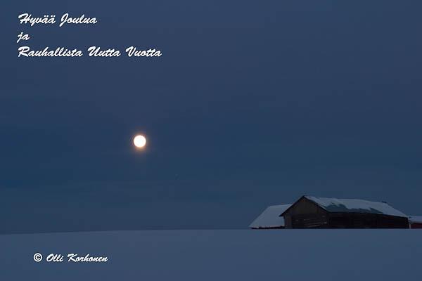 Kuva: Täysikuu lumisen maalaismaiseman yllä.