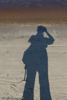 Kuvaajan varjo hiekkarannalla.