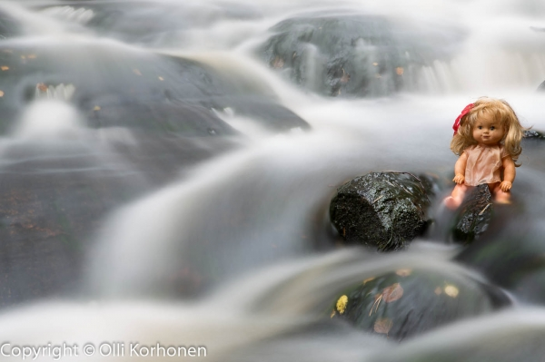 Kuva 3: Nukke istuu kalliolla kuohuvassa koskessa.
