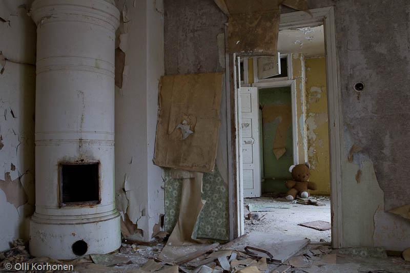 Hylätty Nalle ja aution kivitalon alakerran asuinhuone.