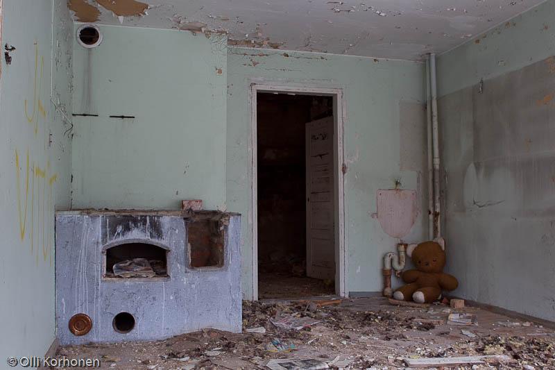 Hylätty Nalle ja aution kivitalon yläkerran vaatimaton keittiö.