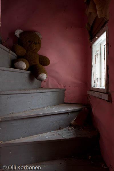 Hylätty Nalle ja autiotalon yläkerran pinkki portaikko.