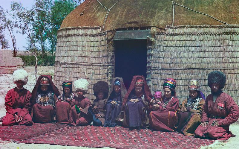 Yhdentoista aikuisen ja lapsen ryhmä istuu matolla jurtan edessä.