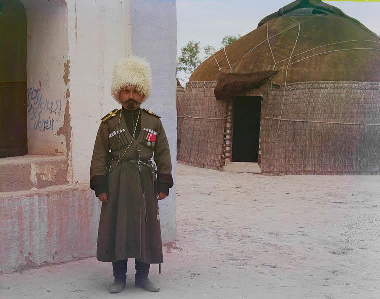 Mies uniformussa, taustalla jurtta.