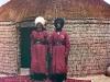 Kaksi miestä seisoo matolla jurtan edessä.